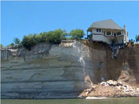 Half of house falls into lake Photo